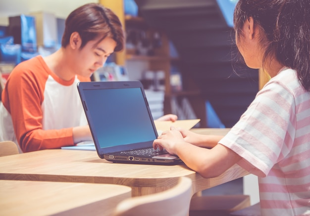 Teenage students studying together use laptop computer