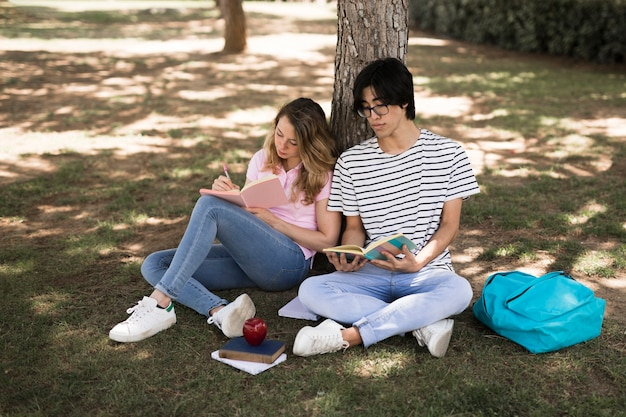 Teenage students with books in park