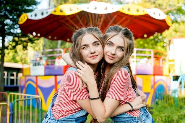 Сестры-близнецы-подростки в ярких обнимающих одеждах, счастливые эмоции, с красочными качелями