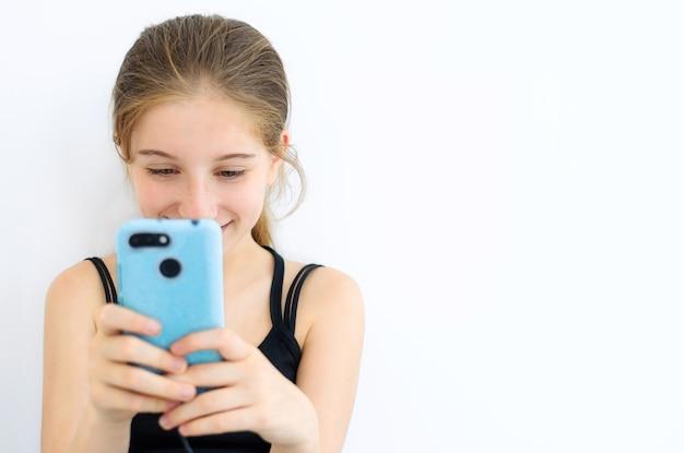 青いスマートフォンでブラウジング10代の女性
