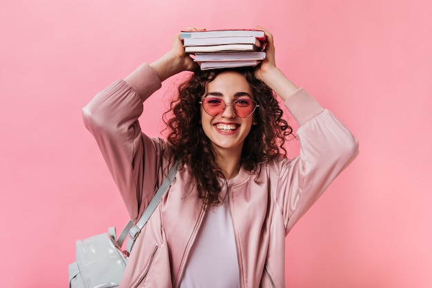 Молодая женщина в розовом наряде позирует с книгами