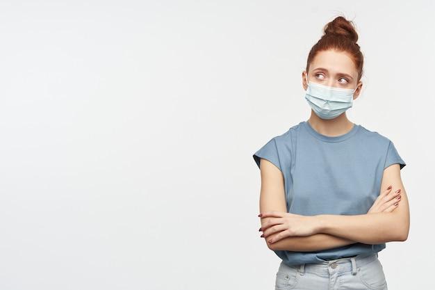 생강 머리를 가진 십대, 궁금해 보이는 여자가 롤빵에 모였습니다. 파란색 티셔츠와 안면 보호 마스크를 착용하십시오. 흰 벽 위에 고립 된 복사 공간에서 왼쪽으로 교차 손으로보고