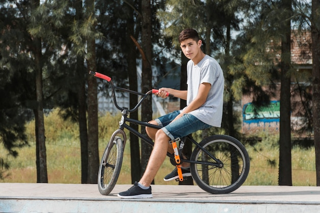 Teenage young boy sitting on bicycle at park