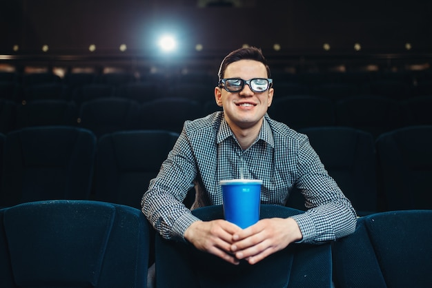 Teenager in 3d glasses holds beverage and poses in cinema. showtime, entertainment industry
