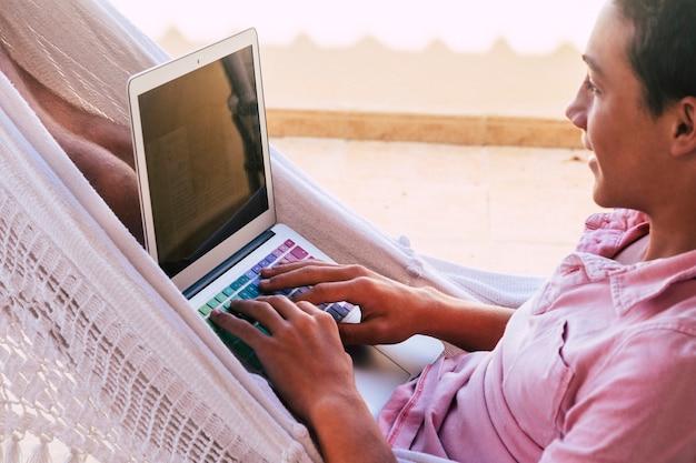 ハンモックのテラスで一人でティーンエイジャーがビデオを探し、ラップトップまたはコンピューターと電話でビデオゲームを操作またはプレイする-オンラインライフスタイルと将来の世代