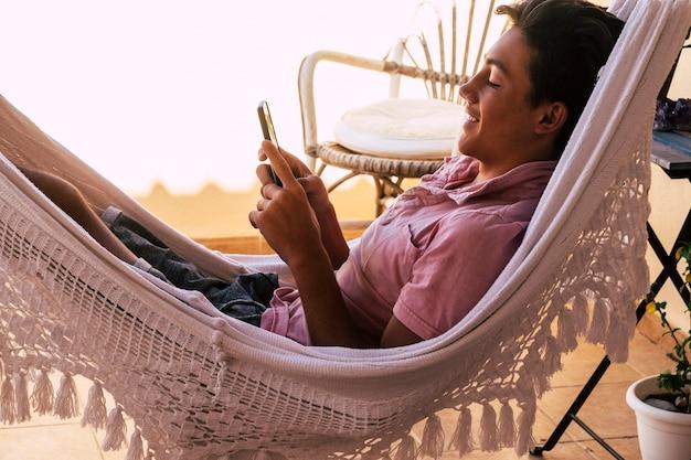ハンモックのように見えるビデオのテラスで10代の若者だけが、自分の携帯電話またはコンピューターと自分の携帯電話でビデオゲームを操作またはプレイします-オンラインライフスタイルと将来の世代