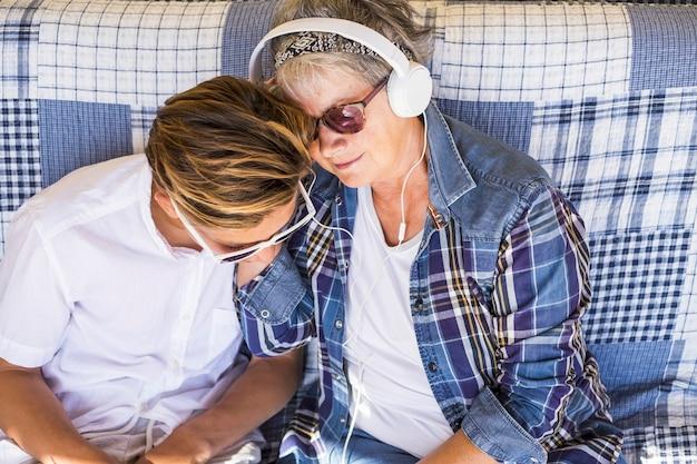 십대와 할머니는 이어폰으로 음악을 듣고 하루를 즐깁니다.