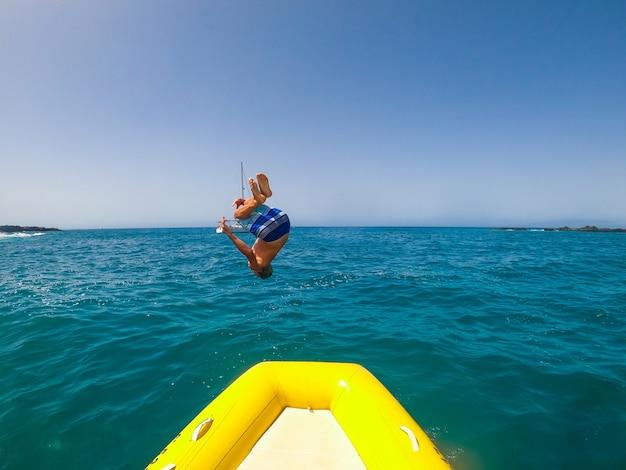 10대와 젊은 남자는 보트를 타고 백플립을 하거나 바다에서 여름 휴가를 즐기고 보트를 빌리는 해변의 백인 사람들