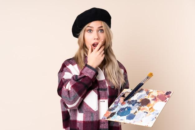 ベージュで分離されたパレットを保持しているティーンエイジャーのアーティストの女の子は、右を見ながら驚いてショックを受けました