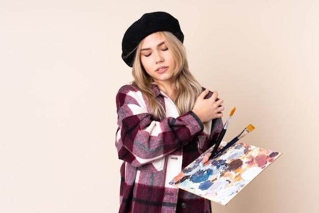 努力したために肩の痛みに苦しんでいる青で隔離のパレットを保持しているティーンエイジャーのアーティストの女の子