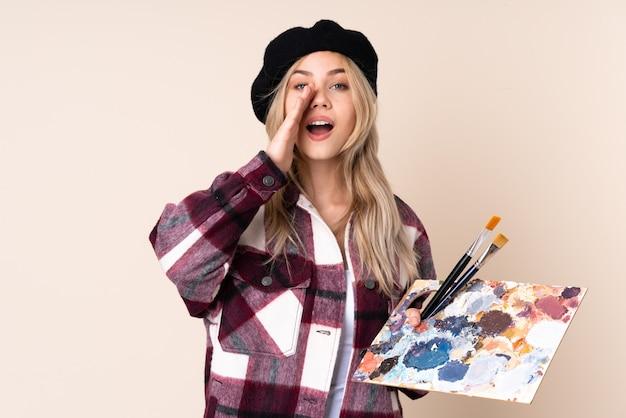青い壁に分離されたパレットを持って叫び、何かを発表するティーンエイジャーのアーティストの女の子