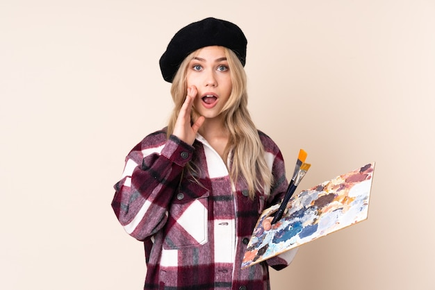 驚きとショックを受けた表情で青い壁に分離されたパレットを保持しているティーンエイジャーのアーティストの女の子
