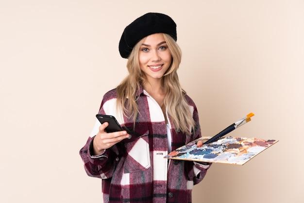 分離されたパレットを保持しているティーンエイジャーのアーティストの女の子