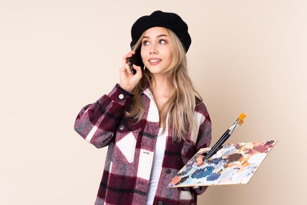 Девушка художника подростка держа палитру на голубой стене держа кофе для того чтобы отнять и мобильный телефон