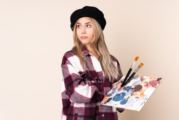 Teenager artist girl holding a palette isolated on blue wall portrait