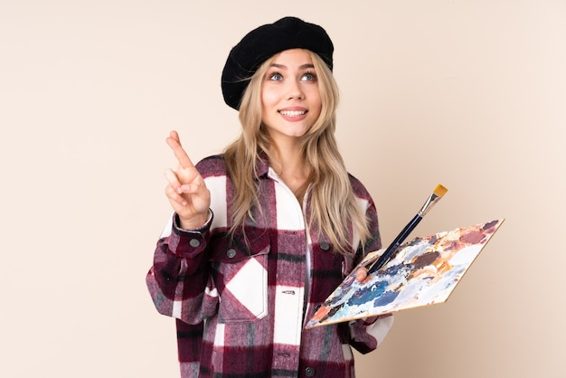Teenager artist girl holding a palette with fingers crossing and wishing the best