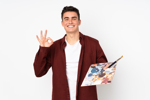 Teenager artist man holding a palette isolated on white wall showing ok sign with fingers