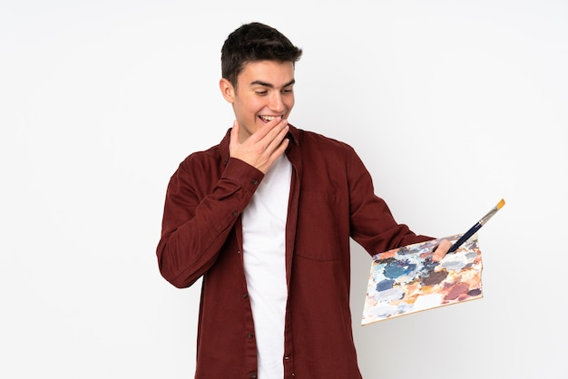 Teenager artist man holding a palette isolated on white with surprise and shocked facial expression