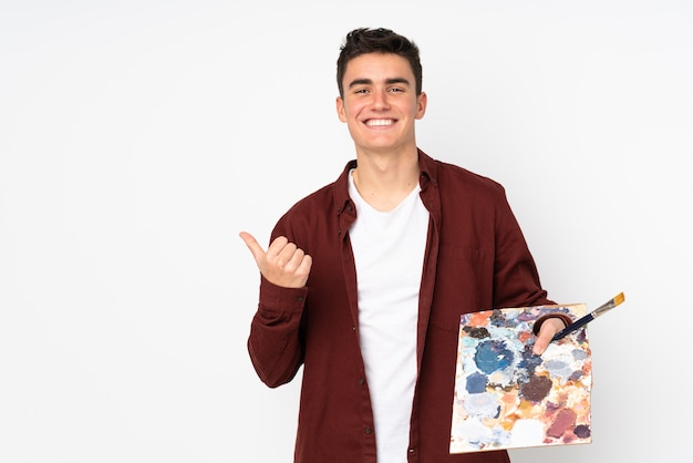Teenager artist man holding a palette isolated on white