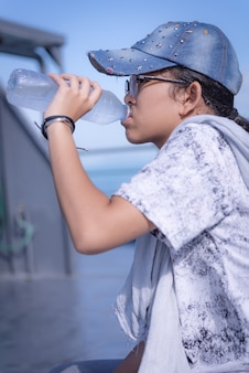 Teenager asian girl drinking water on boat in a sunny day