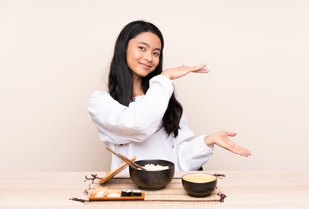 Teenager asian girl eating asian food isolated on beige background holding copyspace to insert an ad