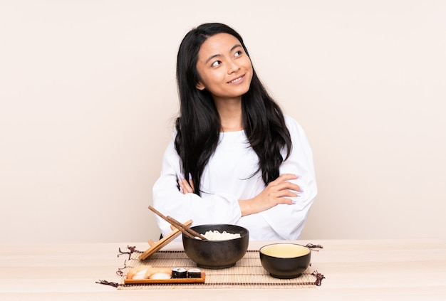 Teenager asian girl eating asian food isolated on beige background looking up while smiling