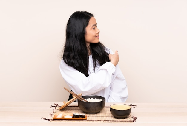 Teenager asian girl eating asian food isolated on beige pointing back
