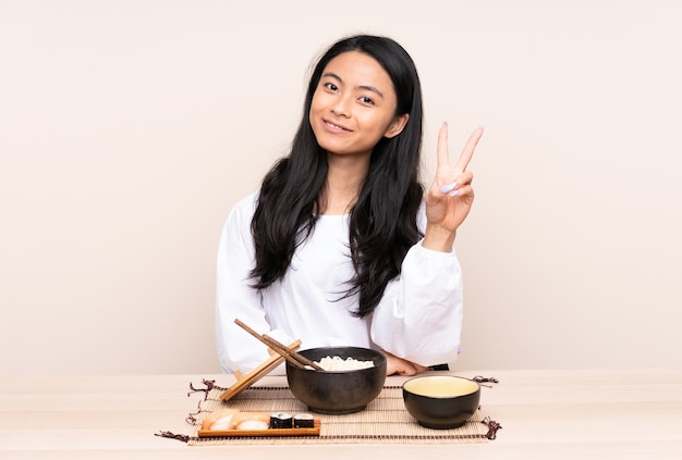Teenager asian girl eating asian food isolated on beige smiling and showing victory sign