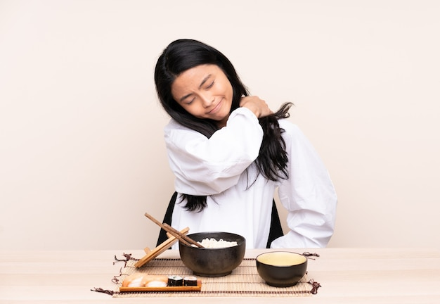 Teenager asian girl eating asian food isolated on beige suffering from pain in shoulder for having made an effort