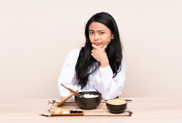 Teenager asian girl eating asian food isolated on beige thinking