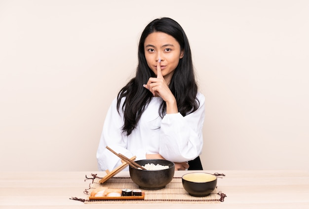 Teenager asian girl eating asian food isolated on beige wall showing a sign of silence gesture putting finger in mouth