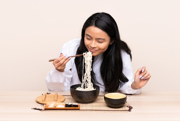 Teenager asian girl eating asian food isolated on beige