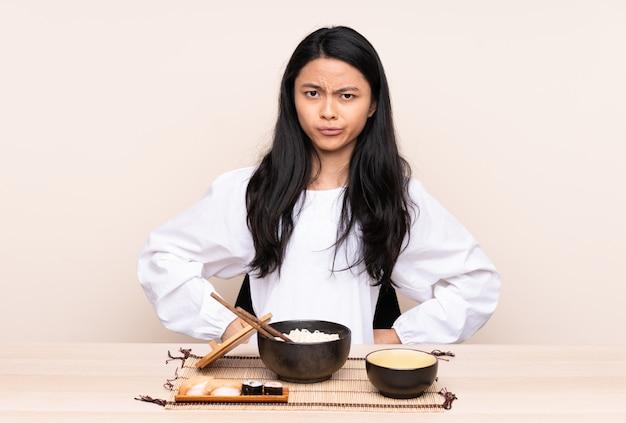 Девушка подростка азиатская есть азиатскую еду изолированную на бежевой предпосылке сердитой