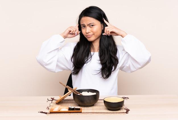 Девушка подростка азиатская есть азиатскую еду изолированную на бежевой предпосылке имея сомнения и думая