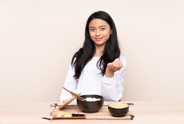 Девушка подростка азиатская есть азиатскую еду изолированную на бежевой предпосылке приглашая прийти с рукой. счастлив, что ты пришел