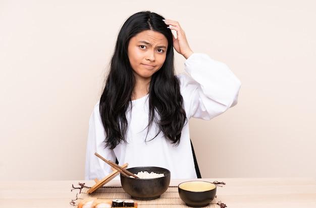 Девушка подростка азиатская есть азиатскую еду изолированную на бежевой предпосылке с выражением разочарования и не понимая