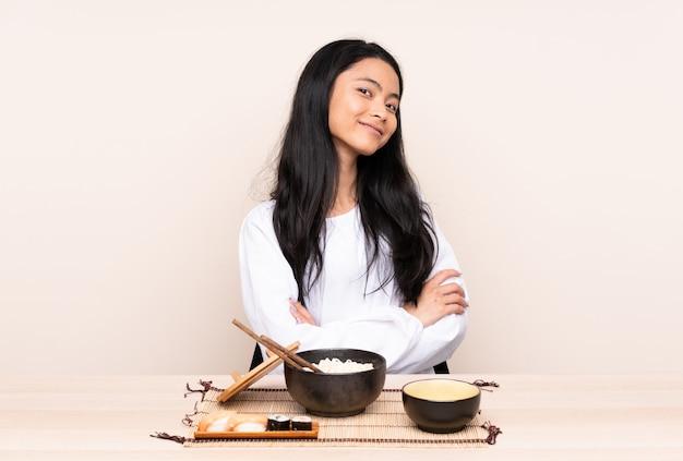 Девушка подростка азиатская есть азиатскую еду изолированную на бежевой предпосылке с оружиями пересекла и счастливая