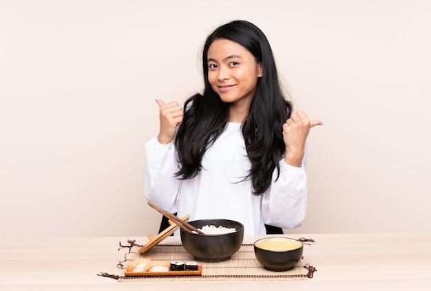 Девушка подростка азиатская есть азиатскую еду изолированную на бежевой предпосылке с большими пальцами руки вверх показывать и усмехаться