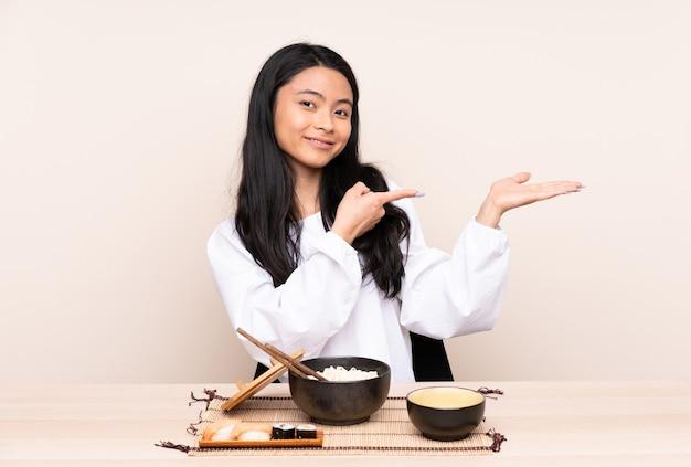 Азиатская девушка-подросток ест азиатскую еду, изолированную на бежевом, держа воображаемую копию пространства на ладони
