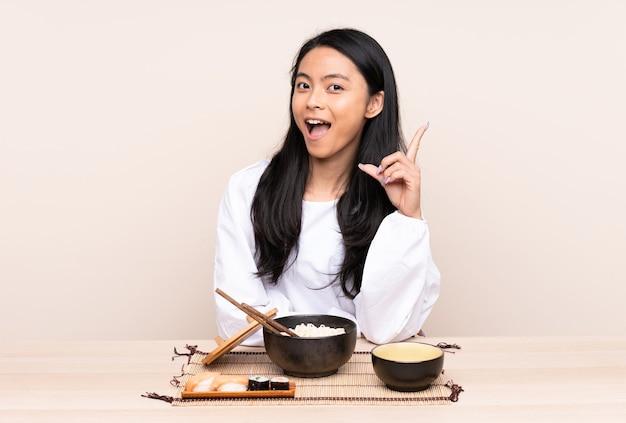 指を上に向けるアイデアを考えてベージュの壁に分離されたアジア料理を食べる10代のアジアの女の子