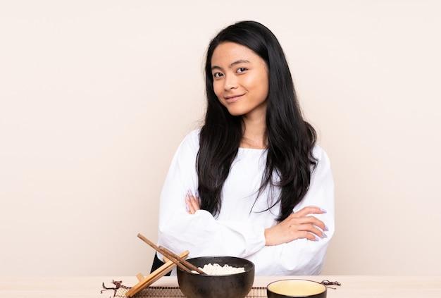 Азиатская девушка-подросток ест азиатскую еду, изолированную на бежевом, со скрещенными руками и с нетерпением жду