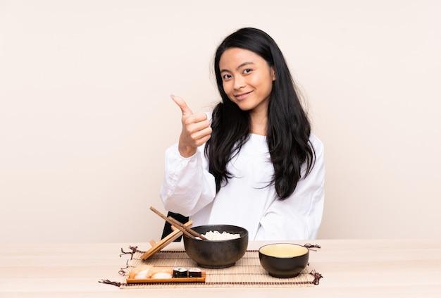 ベージュに分離されたアジア料理を食べる10代のアジアの女の子