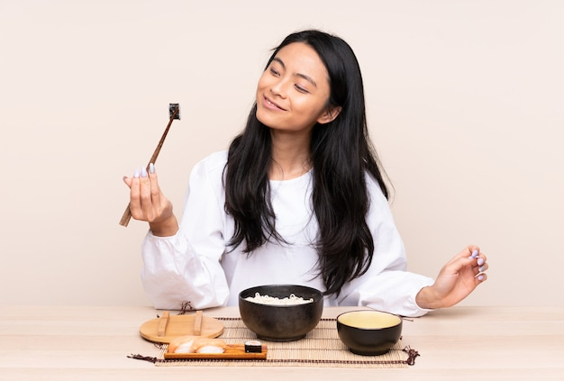 ベージュの壁にアジア料理を食べる10代のアジアの女の子