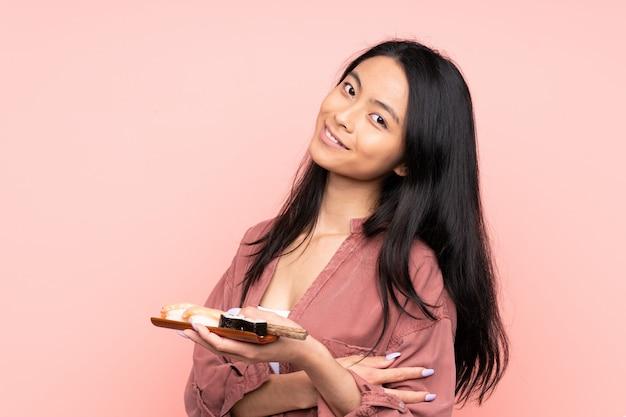 Азиатская девушка подросток ест суши, изолированные на розовом фоне смеется