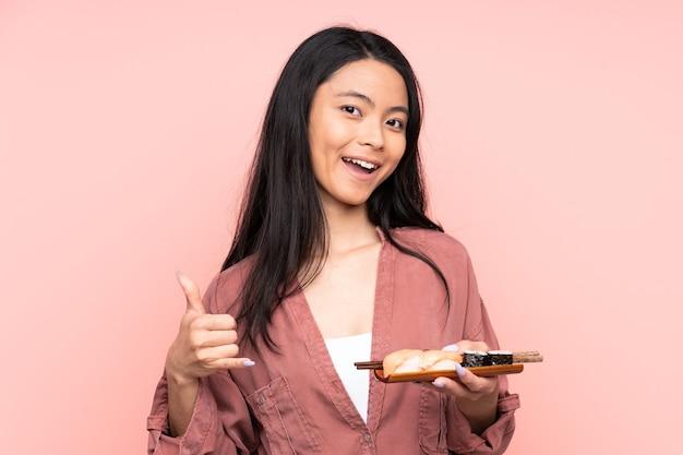 Азиатская девушка подросток ест суши, изолированные на розовой стене, делая жест телефона