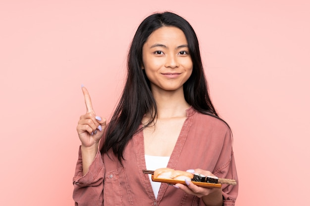 Teenager asian girl eating sushi isolated on pink background pointing with the index finger a great idea