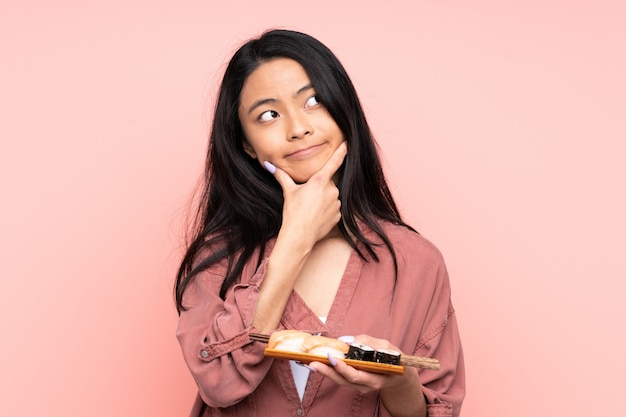 Teenager asian girl eating sushi isolated on pink background thinking an idea