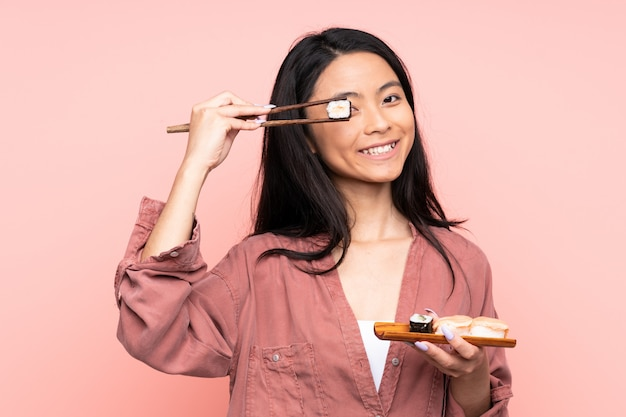 Teenager asian girl eating sushi isolated on pink background