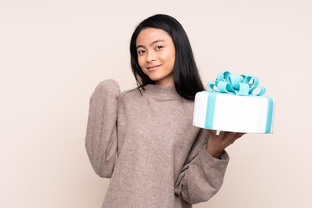 Азиатская девушка-подросток держит большой торт, изолированный на бежевом, указывая в сторону, чтобы представить продукт