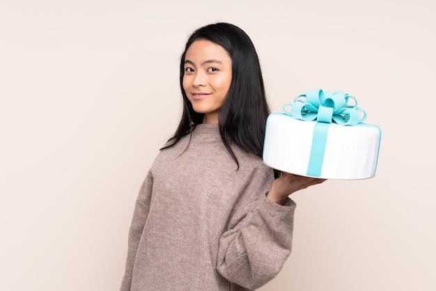 Азиатская девушка подросток держит большой торт, изолированные на бежевый улыбается